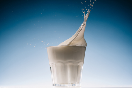 Milk flowing in glass of milk on blue background