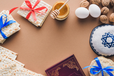 top view of traditional book with text in hebrew, kippah and matza on brown table 写真素材