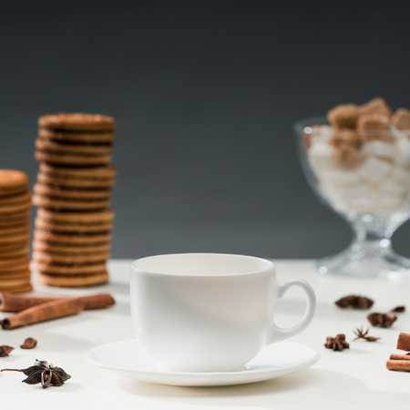 White cup for coffee on table with cookies and spices 版權商用圖片