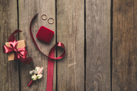flat lay with ribbon, wedding rings, corsage and gift on wooden tabletop Standard-Bild - 99843425