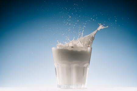 우유와 밝아진 파란색 배경에 고립 된 유리