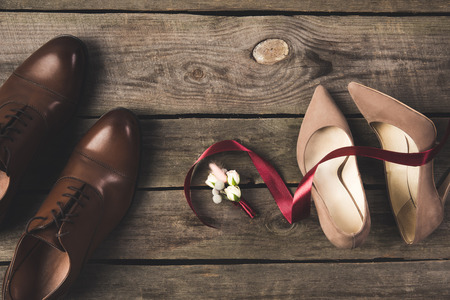 flat lay with bridal  shoes, bow tie, wedding rings on wooden surface Standard-Bild - 99843445