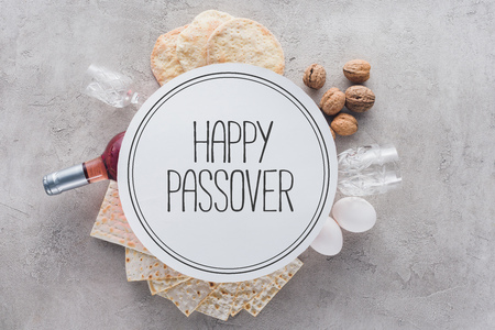 top view of matza and plate with happy passover greeting, jewish Passover holiday concept