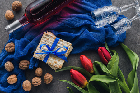 top view of red tulips, wine and matza on table, Pesah celebration concept Stock Photo