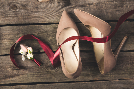 flat lay with ribbon, corsage, bridal and grooms shoes on wooden tabletop Standard-Bild - 99843470