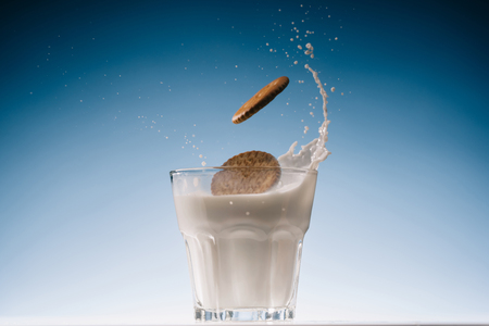 Sweet cookies splashing into glass of milk on blue background 스톡 콘텐츠