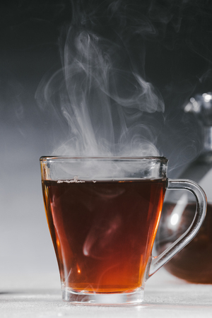 Steaming black tea in glass cup on table
