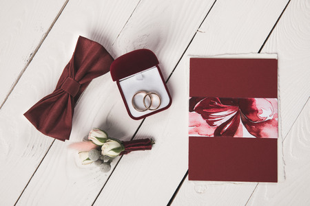 flat lay with buttonhole, bow tie and jewelry box on wooden surface Stock Photo