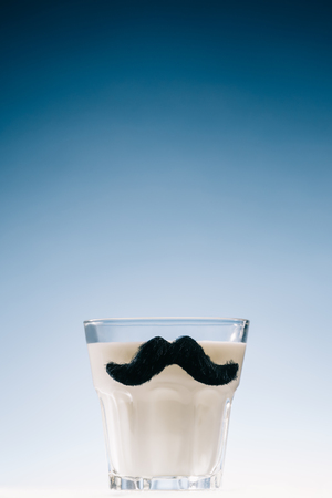 Transparent glass with mustaches filled with milk isolated on blue background Stockfoto - 99843529