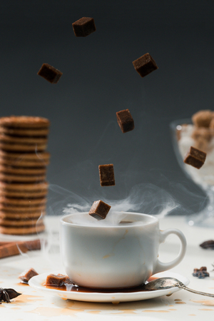 Steaming coffee cup with falling cane sugar cubes by cookies on table