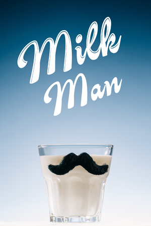 Glass of milk with mustaches and Milk man inscription isolated on blue background
