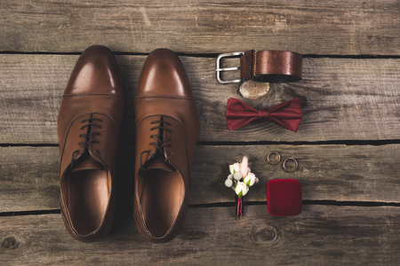 flat lay with arranged grooms accessories and wedding rings on wooden tabletop Standard-Bild - 99843542