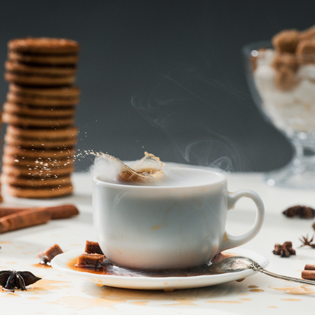 Brown sugar cubes splashing into coffee cup on table with cookies and spices