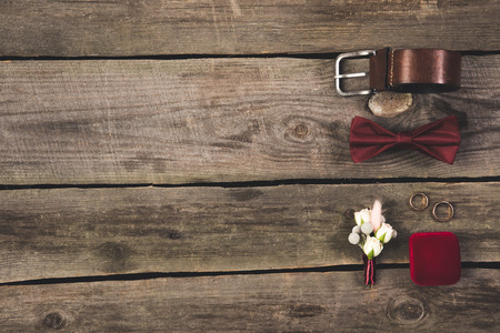 flat lay with arranged grooms accessories and wedding rings on wooden tabletop Standard-Bild - 99843567