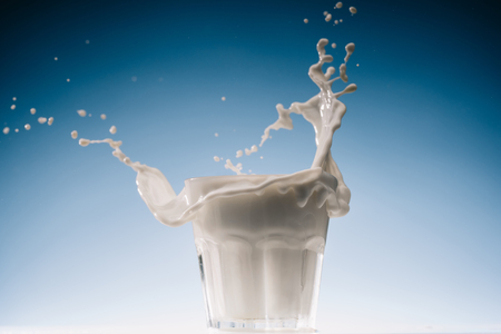 Glass of milk with large splashes isolated on blue background 스톡 콘텐츠