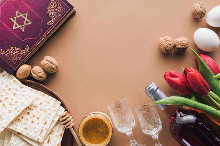 top view of traditional book with text in hebrew, honey and matza on brown table