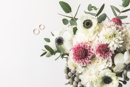 top view of beautiful bridal bouquet and wedding rings isolated on grey