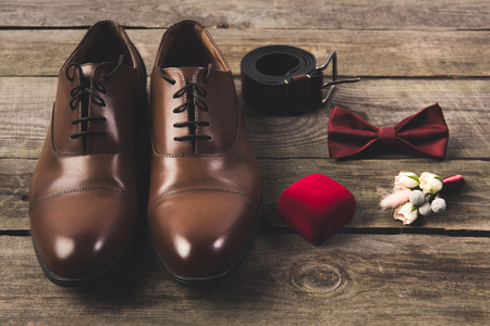 close up view of arranged grooms shoes and accessories on wooden surface Standard-Bild - 99843620