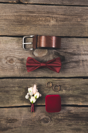 flat lay with arranged grooms accessories and wedding rings on wooden tabletop Standard-Bild - 99843632