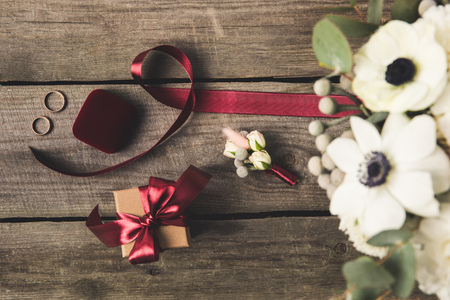 flat lay with ribbon, wedding rings, corsage and gift on wooden tabletop Standard-Bild - 99843634