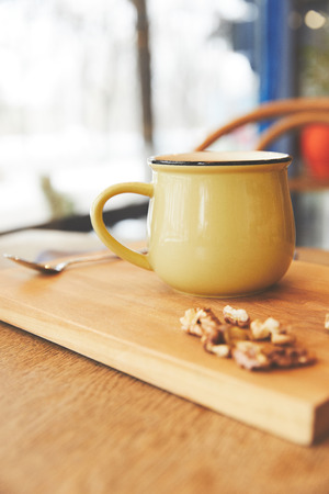 Hot cocoa in mug with nuts served on wooden board