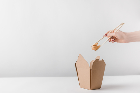 cropped image of woman holding chinese fortune cookie with chopsticks