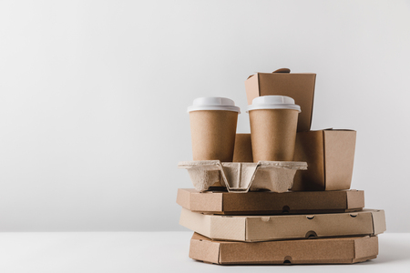 pizza boxes and disposable coffee cups with noodles boxes on table