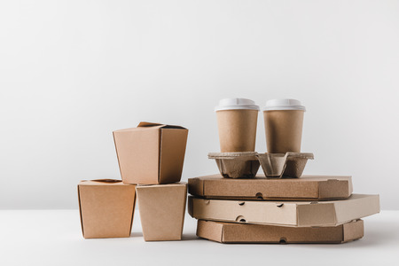 pizza boxes and disposable coffee cups with noodles boxes on surface
