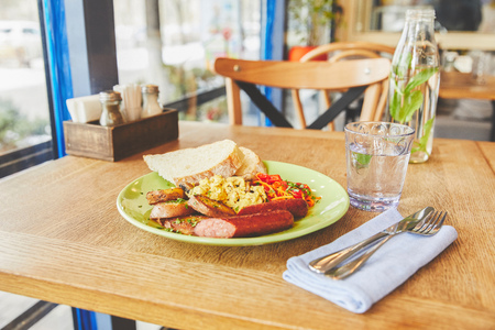 Breakfast with fried eggs served with vegetables ans sausage in plate Stock Photo
