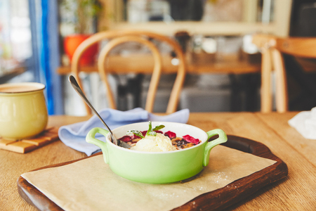 Berry crumble served in pot on table with coffee Stock Photo