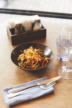 Hot delicious udon noodles with pork on restaurant table Banco de Imagens