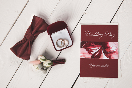 flat lay with invitation, buttonhole, bow tie and jewelry box on wooden tabletop Stock Photo