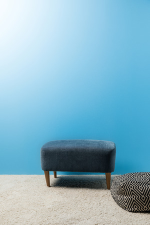 hassock standing on carpet in front of blue wall