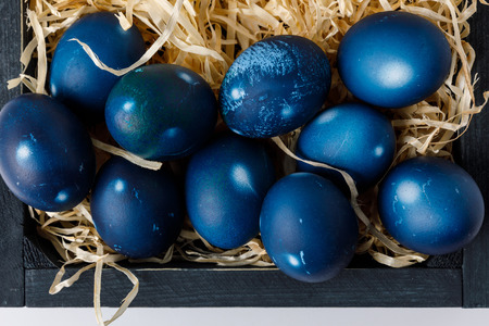 top view of blue painted easter eggs in wooden box with decorative hay