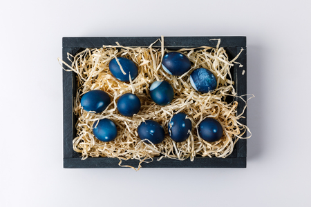 top view of blue painted easter eggs in wooden box with decorative hay on white Stock Photo