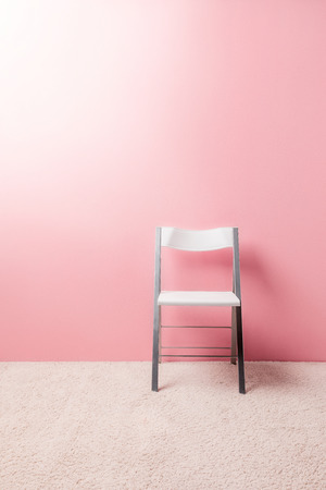 foldable chair in front of pink wall