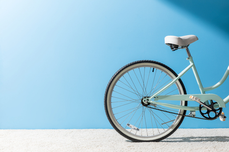 back wheel of bicycle standing on carpet in front of blue wall Stock fotó