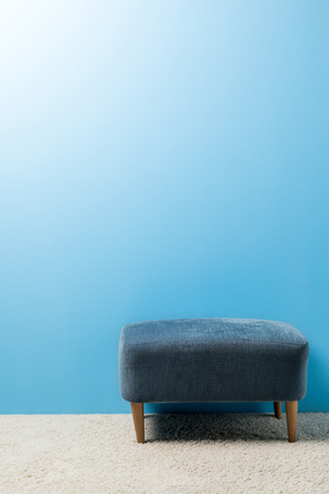 soft hassock standing on carpet in front of blue wall Stock Photo