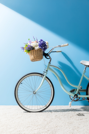 bicycle with beautiful flowers in basket in front of blue wall