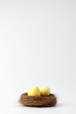 yellow painted easter eggs in decorative nest on white