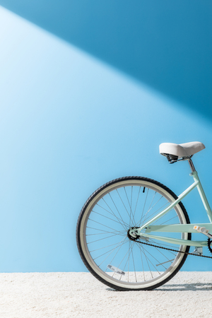 back wheel of bicycle in front of blue wall Stock fotó