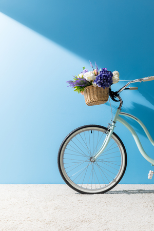 bicycle with flowers in basket standing on carpet in front of blue wall Stock fotó