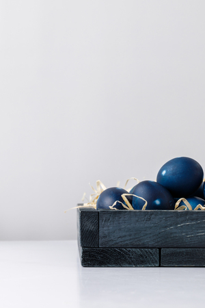 blue painted easter eggs in box with decorative hay