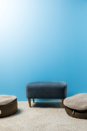 comfy hassocks in front of blue wall Stock Photo