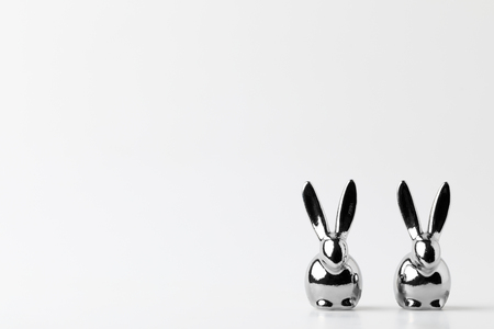 two statuettes of silver easter bunnies on white 免版税图像