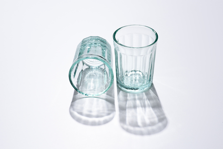 close up view of empty glasses and shadows on white surface