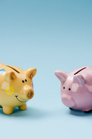 close up view of two yellow and pink piggy banks isolated on blue 版權商用圖片 - 100429213