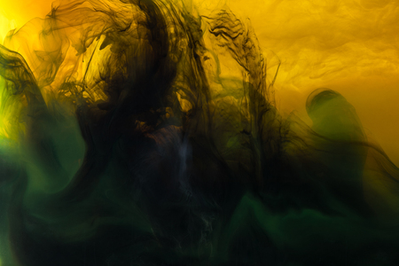 full frame image of mixing of yellow, green and black paints splashes  in water Stock Photo
