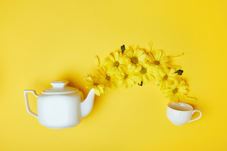 Yellow chrysanthemums pouring into cup from white pot isolated on yellow Stock Photo