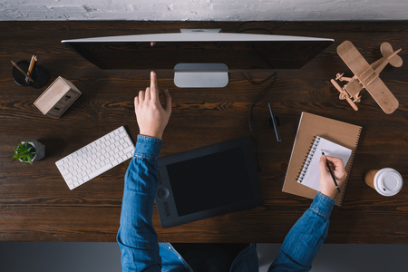 cropped shot of person using desktop computer and taking notes at workplace Stock Photo